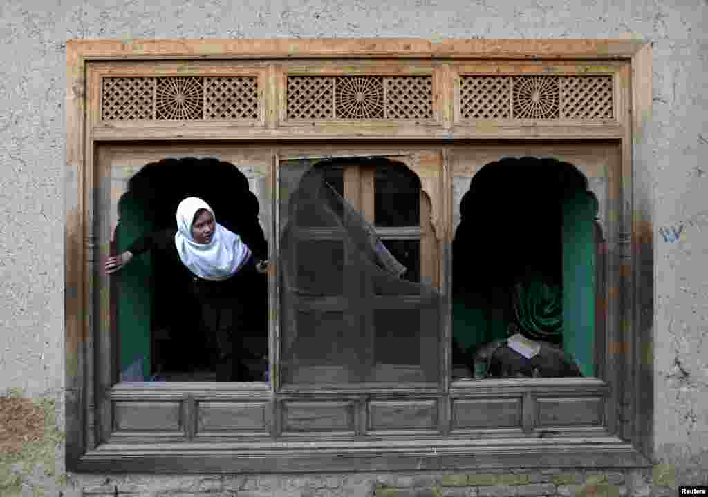 An Afghan girl looks out of a damaged window of a shrine after a suicide attack in Kabul on March 25. (Reuters/​Mohammad Ismail)