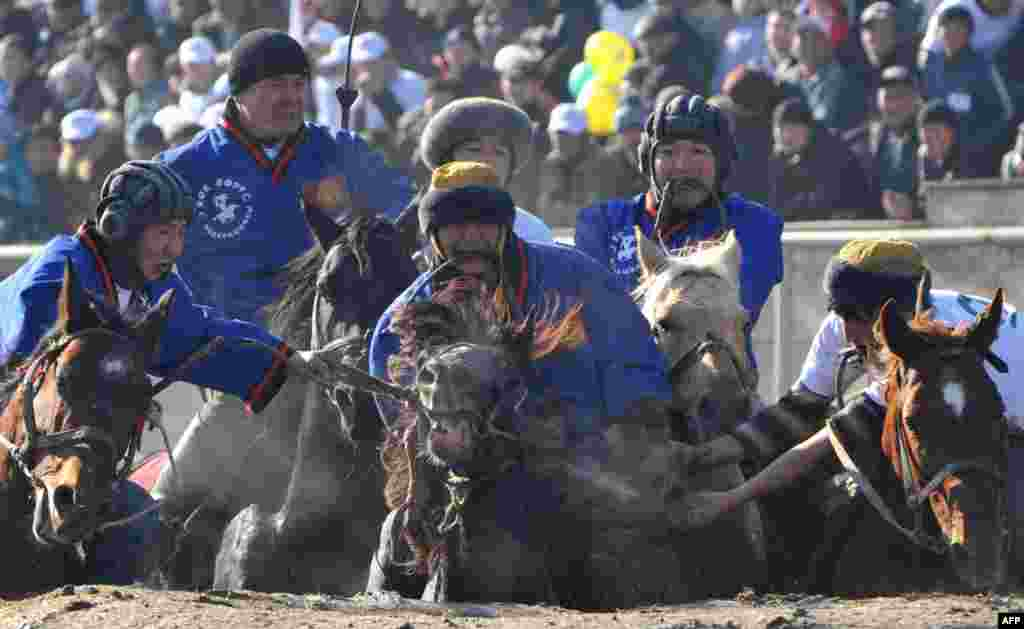 Riders play the traditional Central Asian sport of buzkashi in Bishkek, the capital of Kyrgyzstan. Mounted players compete for points by throwing a stuffed sheepskin into a well. (AFP/Vyacheslav Oseledko)