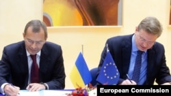 Ukrainian Deputy Prime Minister Andriy Klyuyev (left) and EU Enlargement Commissioner Stefan Fuele sign documents at EU headquaretrs in Brussels.