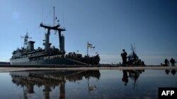 Marinarii ucraineni de la vasul Slavutici se uită lmilitarii ruși care patrulează în portul Sevastopol, 5 martie 2014.