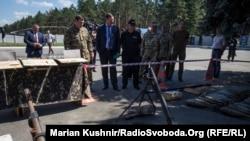 Юрій Луценко дивиться на виставлену зброю, якою мали б скористатися для теракту Рубан та Савченко
