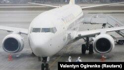 Співробітники аеропорту одягнені у захисні костюми, щоб дезінфікувати літак МАУ, «Бориспіль», Україна