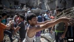Палестинцы ищут выживших в руинах дома, разрушенного во время авианалета израильских ВВС, Газа, 4 августа 2014 года.