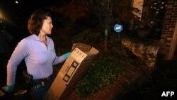 Агент ФБР выносит коробку после обыска в доме Полы Бродвелл