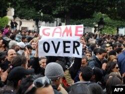 """Тунис астанасындағы халық толқуынан көрініс. Демонстранттар елдің президентіне қаратып """"Саудаң бітті!"""" деген плакат ұстап тұр. Тунис, 14 қаңтар 2011 жыл"""