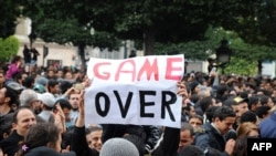 "A demonstrator holds a sign reading ""Game Over"" during a rally in front of the Interior Ministry in Tunis on January 14."