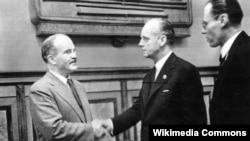 Вячаслаў Молатаў (зьлева) цісне руку Яахіму фон Рыбэнтропу пасьля падпісаньня дамовы. Масква, 23 жніўня 1939 г.