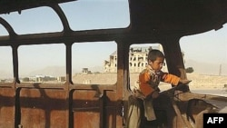 An Afghan boy plays in the remains of a Soviet bus in Kabul (file photo)