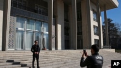 In this Jan. 15, 2019 photo, men take pictures while visiting Niavaran Palace, now a museum, that was the primary and last residence of late Shah Mohammad Reza Pahlavi and his family prior to leaving Iran for exile in 1979.