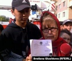 Багжан Аязбекова (справа) после акции протеста на кране показывает журналистам протест генеральной прокуратуры с требованием пересмотреть дело ее осужденного сына Азамата Аязбекова. Слева - ее сноха Гулим Бабакова. Астана, 4 июня 2013 года.