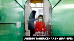 IRAN SCHOOLS PANDEMIC CORONAVIRUS COVID19 -- An Iranian elementary school girl wearing a face mask passes by a disinfection tunnel as she attends the first day of reopening the Bamdad Parsi private school, north of Tehran, Iran, 05 September 2020. Media