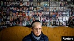 Harja Ćatić sedi ispred zida na kojem su postavljene fotografije žrtava genocida u Srebrenici
