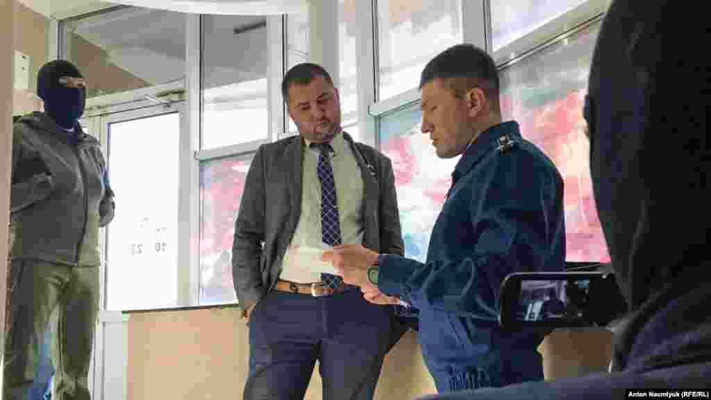 Адвокат Эмиль Курбединов беседует с российским полицейским
