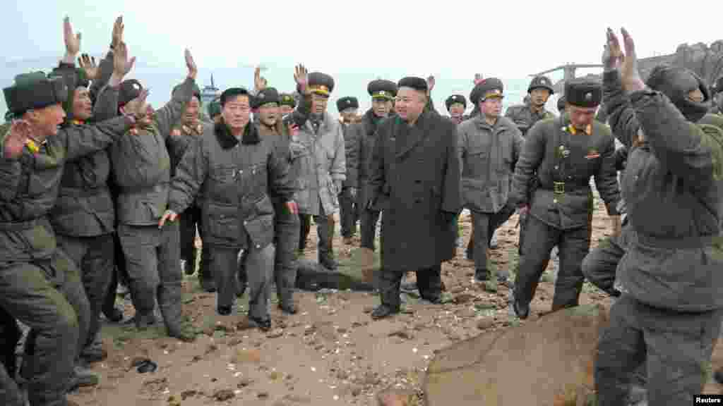 North Korea leader Kim Jong Un (center) is greeted by soldiers during his visit to a defense detachment near the border with South Korea. (Reuters/KCNA)