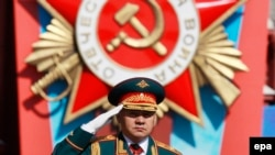 Russian Defense Minister Sergei Shoigu salutes as he reviews the troops during a military parade marking the 69th anniversary of the victory over the Nazi Germany in the WWII on Red Square in Moscow on May 9, 2014.