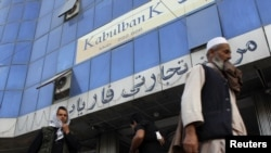 People walk past Kabul Bank branch in Kabul