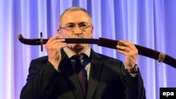 Russian former oil tycoon Mikhail Khodorkovsky receives a replica of a saber after he was awarded with the Knight of Freedom award by the Kazimierz Pulaski Foundation in Warsaw on December 3.