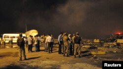 Security officials and airport staff visit the site damaged by Taliban attack on Jinnah International Airport in Karachi, June 9, 2014.