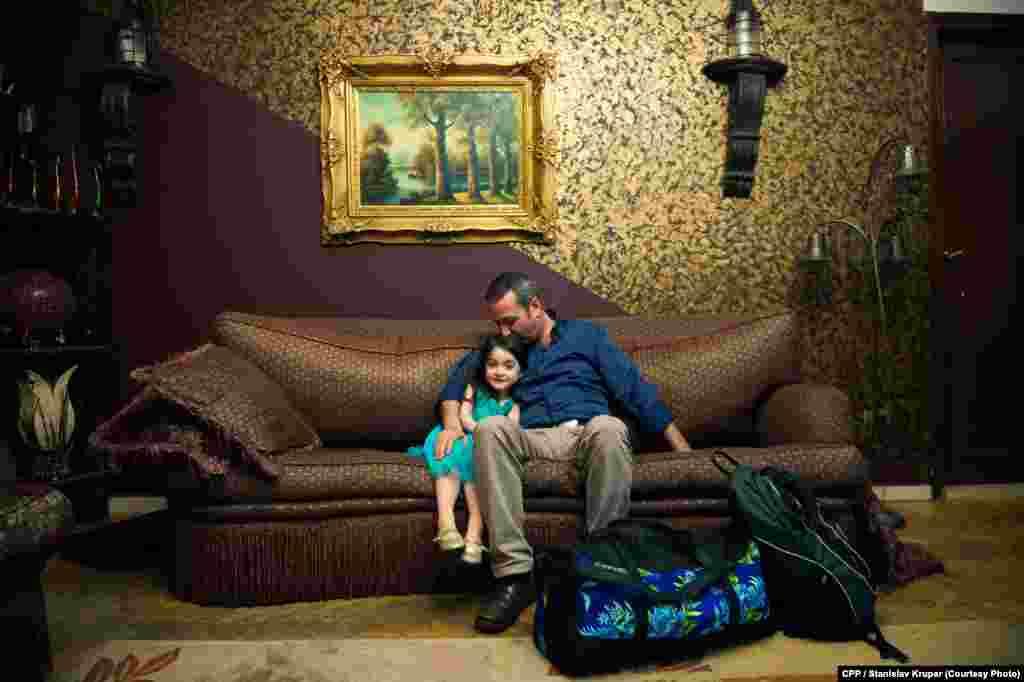 """Anas Abduldayem, një sirian, që rri ulur me vajzën e tij në ditën që ai la familjen e tij në Kajro, në një përpjekje e sipërpër të emigruar në Itali me anije. Çmimi i Parë, kategoria """"Lajme tëPërgjithshme"""",nga freelanceri Stanislav Krupar."""