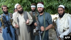 Taliban militants stand with residents as they took to the street to celebrate the cease-fire on the second day of Eid in the outskirts of Jalalabad on June 16.