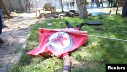 Turkey -- A victim, with a flag of the left-wing Federation of Socialist Youth Associations covering him, lies on the ground following an explosion in Suruc, in the southeastern Sanliurfa province, July 20, 2015.