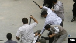 Men in civilian clothes beat a protester during a demonstration on June 14.