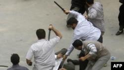 نیروهای لباس شخصی در حال زدن یکی از معترضان