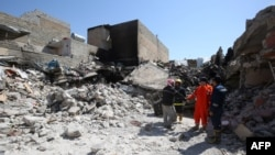 Iraqi civilians and rescue workers inspect the damage in Mosul following an air strike on March 26.