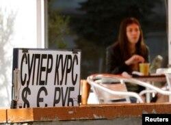Кафедегі валюта бағамы жарнамасының жанында отырған әйел. Қырым, Севастополь, 24 наурыз 2014 жыл. (Көрнекі сурет)