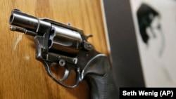 A Mark David Chapman által használt gyilkos fegyver a merénylő fotója mellett látható egy kiállításon New Yorkban.