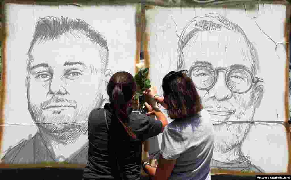 Az áldozatok portréi előtt helyeznek el fehér rózsákat a hozzátartozók 2021. augusztus 3-án.