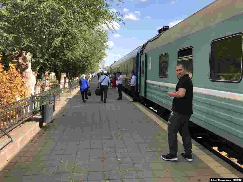 Теміржол вокзалы перронында тұрған пойыз бен жолаушы.