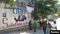 Ljudi prolaze pored zida na kojem je prikazan predsednik Haitija, Port-au-Prince na Haitiju 7. jula 2021.