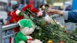 RUSSIA - A woman lays flowers near a school after a shooting in Kazan, Russia, Tuesday, May 11, 2021