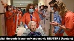 Медицинские работники приветствуют 104-летнюю Елену, когда она выходит из больницы Грегорио Маранон после лечения от коронавирусной болезни (COVID-19) и выписки в Мадриде.