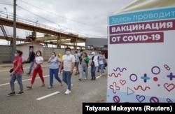 Трудовые мигранты идут в центр вакцинации от COVID-19 на городском рынке в Москве. 30 июня 2021 года. Фото: Reuters.