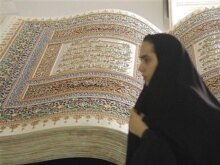 Iran - A woman passes by a sculpture of an open holy Koran during the annual Koran exhibition in Tehran, 17Sep2007
