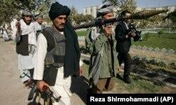 Foști luptători talibani merg să predea armele autorităților afgane din Herat, la vest de Afganistan, duminică, 31 octombrie 2010.