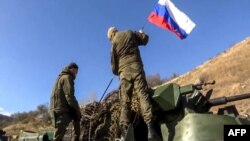 Two soldiers attaching a flag on the Russian peacekeeping forces' military vehicle as they move on the road towards Martuni in Nagorno-Karabakh. November 13, 2020.