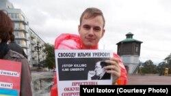 """Jurij Izotov a szeparatizmus vádjával bebörtönzött krími tatár vezető, Ilmi Umerov szabadon engedéséért tüntet. """"A megszállás a bűntett, nem az ellene való tüntetés"""" ‒ áll a feliraton"""