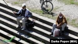 Луѓе со заштитни маски рибарат на брегот на Вардар во Скопје