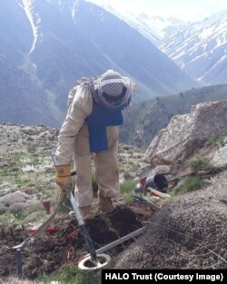 A civilian deminer from HALO Trust uses a metal detector to search for Soviet-era landmines and unexploded ordnance in the mountains of Afghanistan.