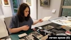 Кураторът Свобода Цекова реди част от снимките в изложбата.