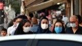 IRAN -- Iranians wearing face masks walk on a street of Tehran, September 24, 2020