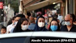 IRAN -- Iranians wearing face masks walk on a street of Tehran, September 24, 2020