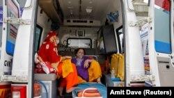 Пациентка с кислородной маской в машине скорой помощи в Индии.