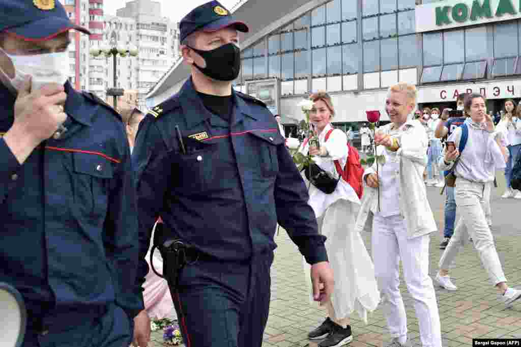 Anti-government protesters offer flowers to two police officers in Minsk on August 12.