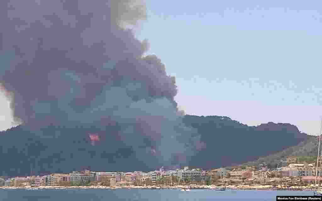 A plume of smoke is seen filling the sky of the coastal resort of Marmaris, as wildfires erupted across Turkey's coast, July 29, 2021, in this screen grab taken from a video.