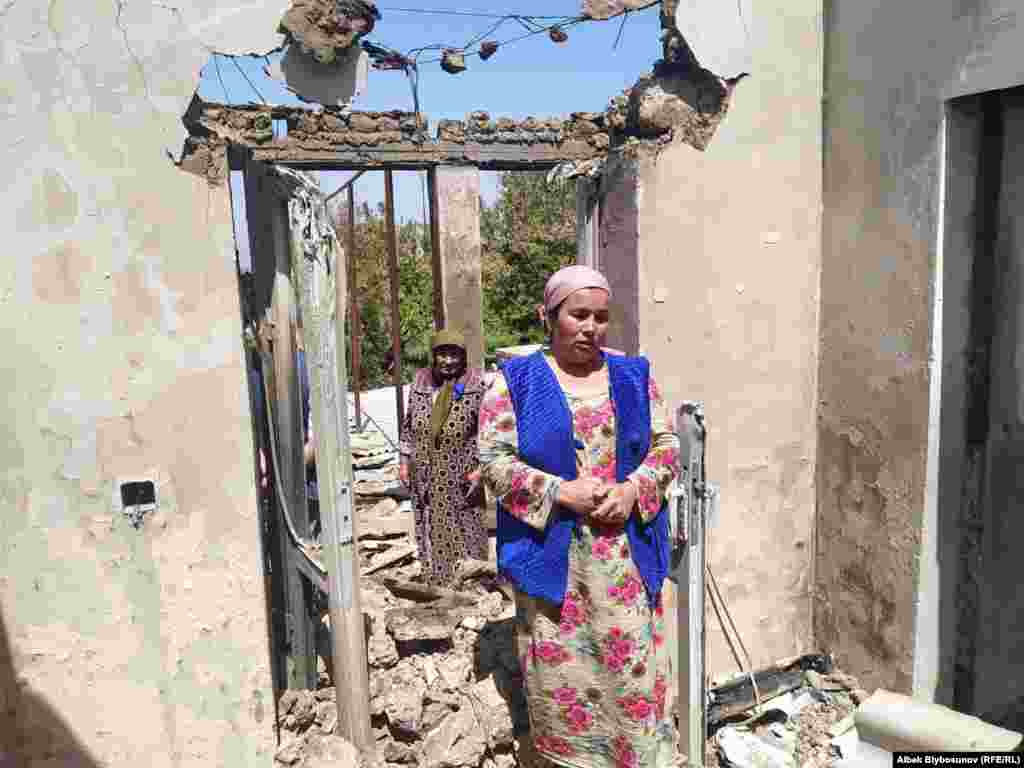 A woman stands in front of her destroyed home in the Kyrgyz village of Maksat. According to Bishkek, 78 private homes were destroyed in Kyrgyzstan's southwestern region of Batken.