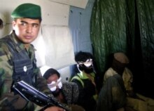 Afghanistan -- Afghan Nat'l Army soldier escorts Pakistani and Afghan self-confessed Taliban prisoners, 18Oct2006